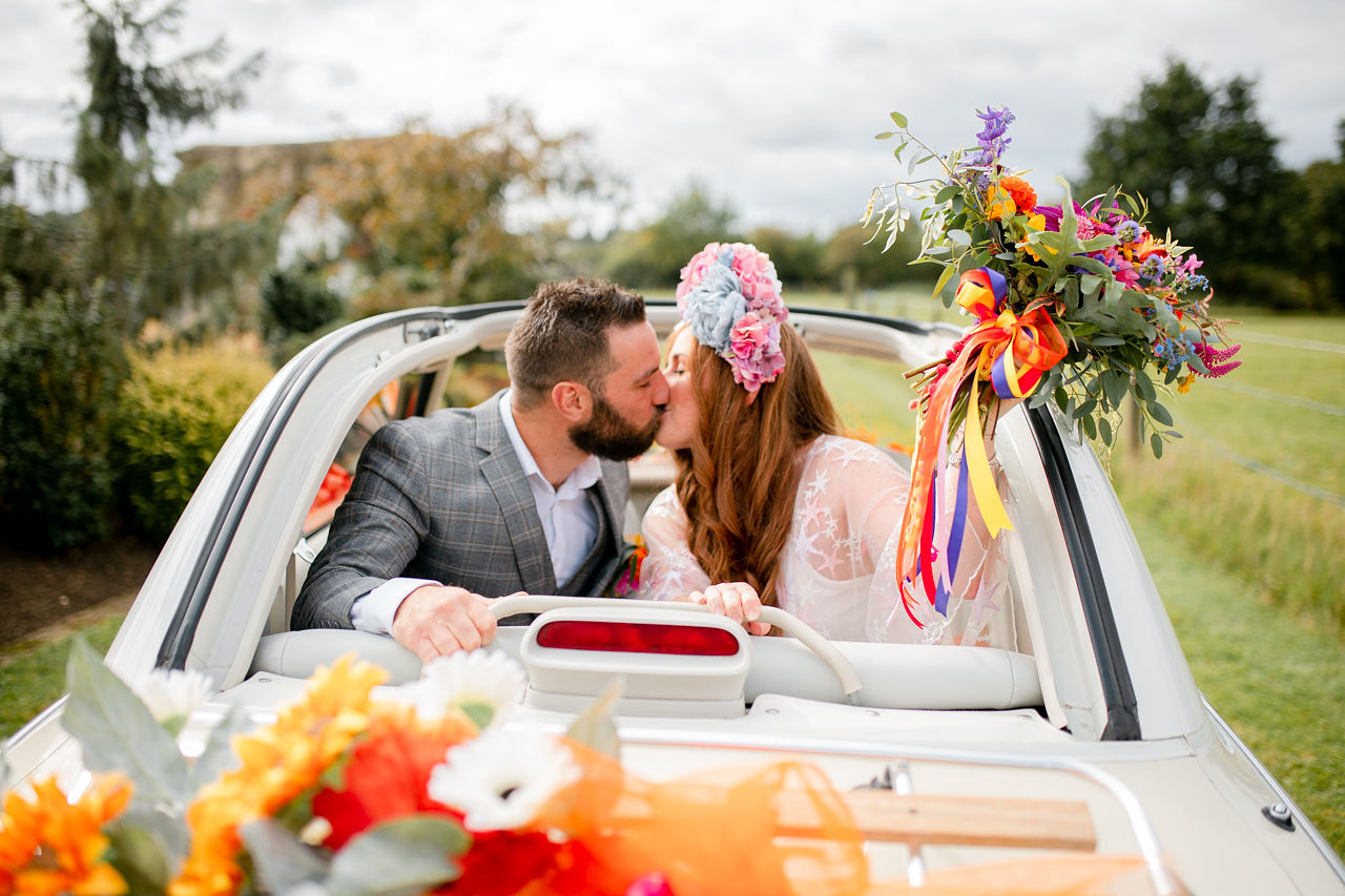 outdoor rainbow wedding - couple in vintage wedding car