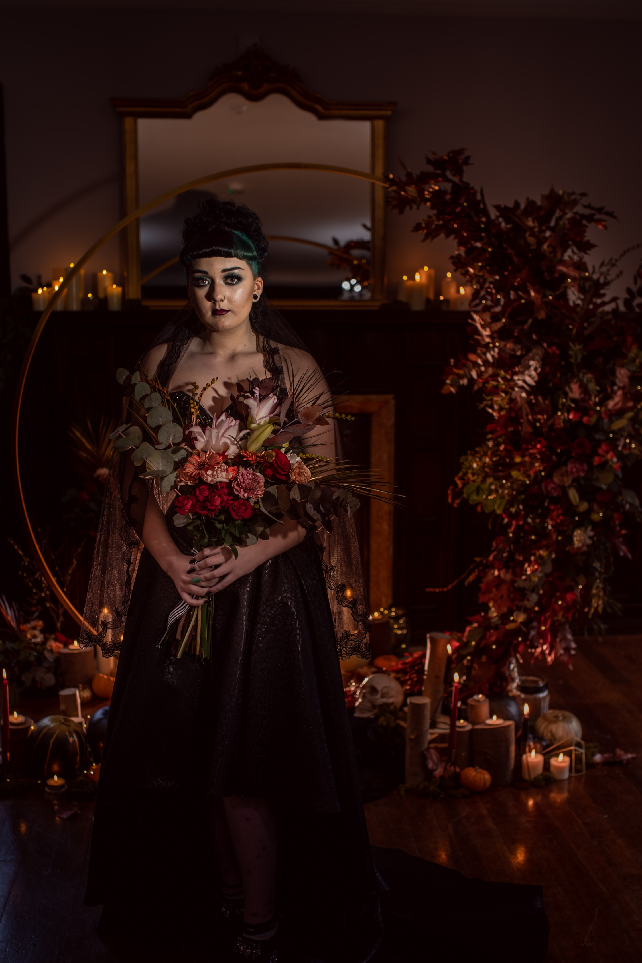 halloween bride - gothic halloween wedding set up - bride standing in front of dramatic floral arch in the candlelight with wedding bouquet - autumn colours of gold, copper and black