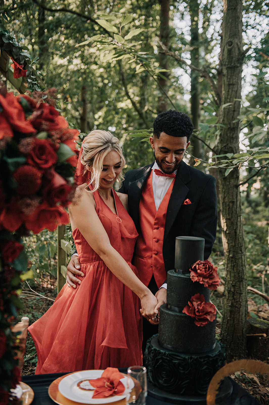 red wedding - red wedding dress - black wedding cake - forest wedding - cutting the cake