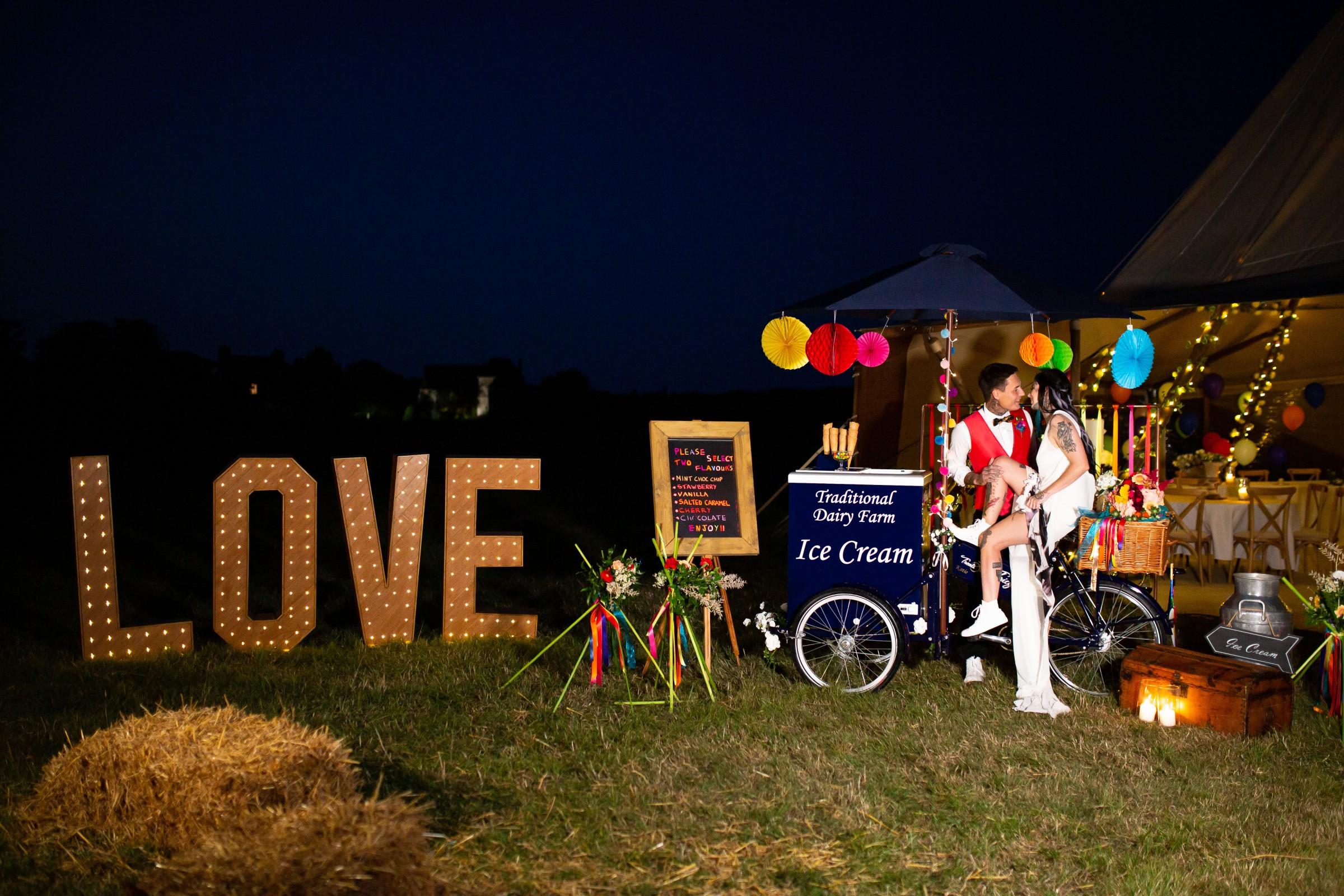 rainbow festival wedding - colourful wedding - quirky wedding ideas - love light up sign - wedding ice cream cart