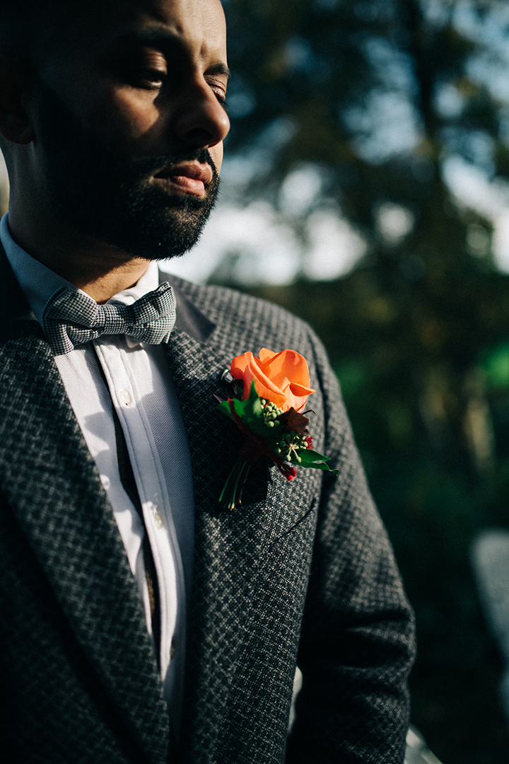 unique grooms suit with red flower
