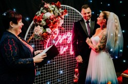 The secret bunker - north west alternative wedding venue - cheshire wedding venue - quirky wedding venue - celebrant wedding with neon backdrop and couple exchanging vows