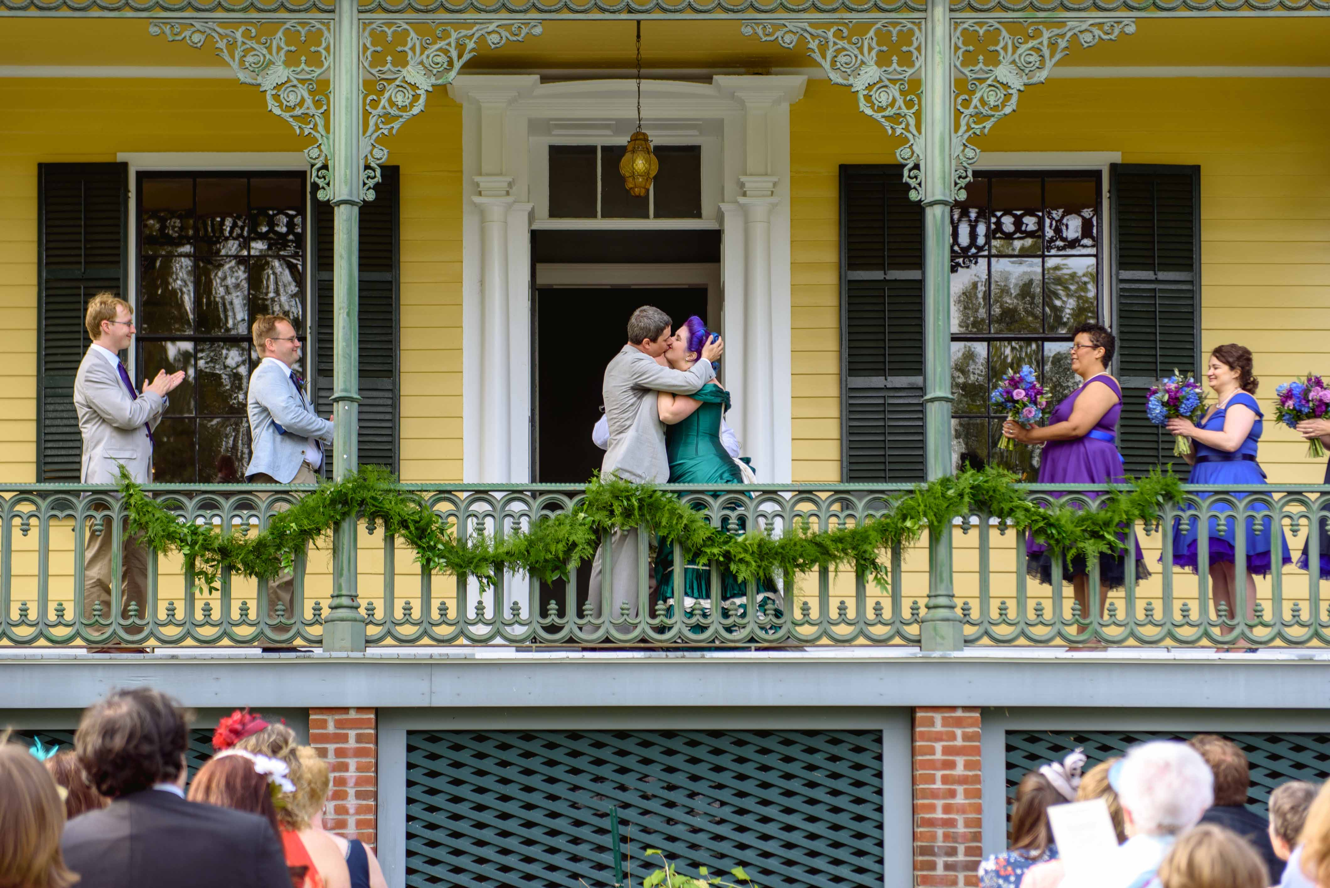 bride and groom kiss on balcony - fun wedding photos - unconventional wedding