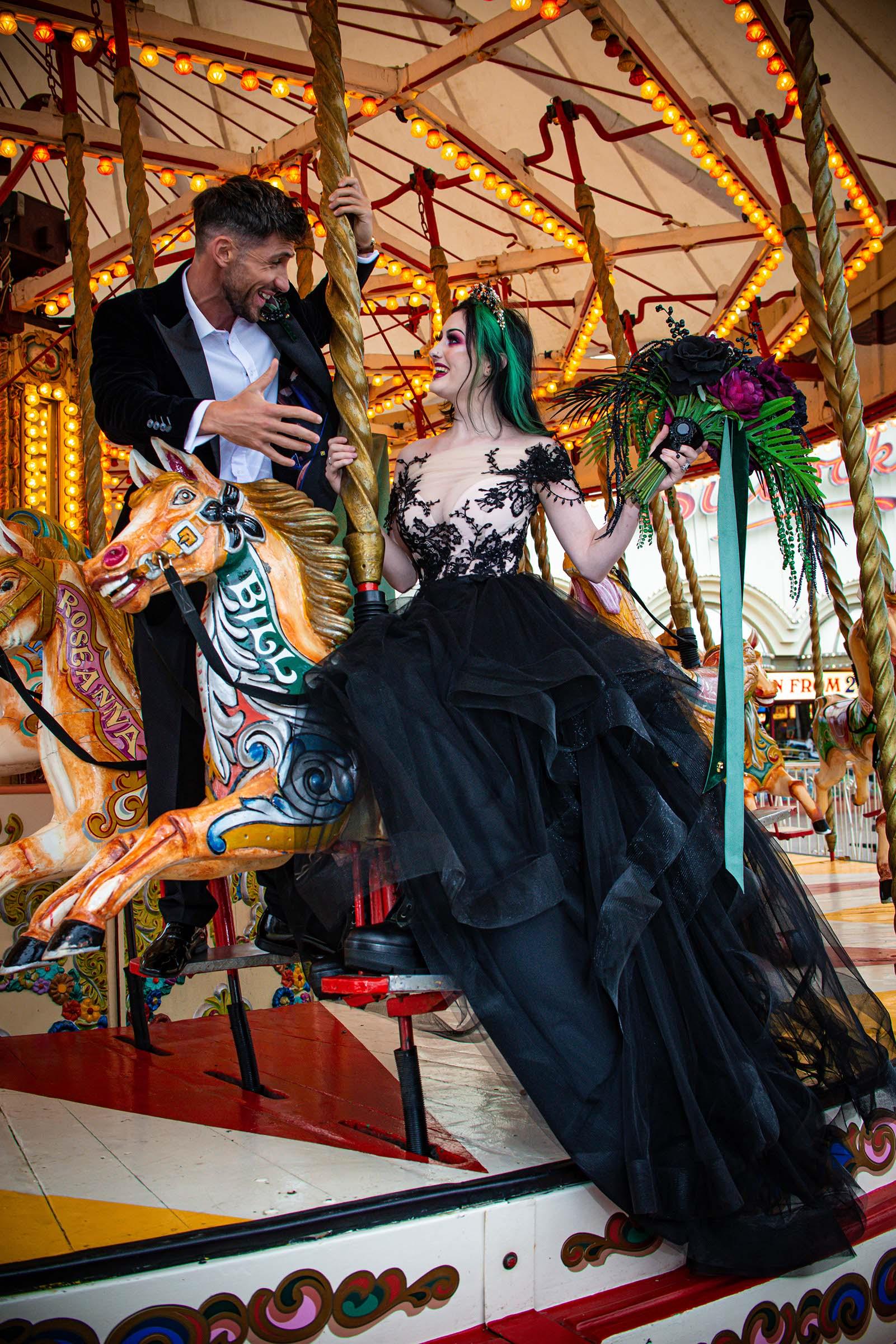 alternative luxe wedding - slytherin wedding - gothic wedding - alternative wedding - fun wedding ideas - bride and groom on carousel