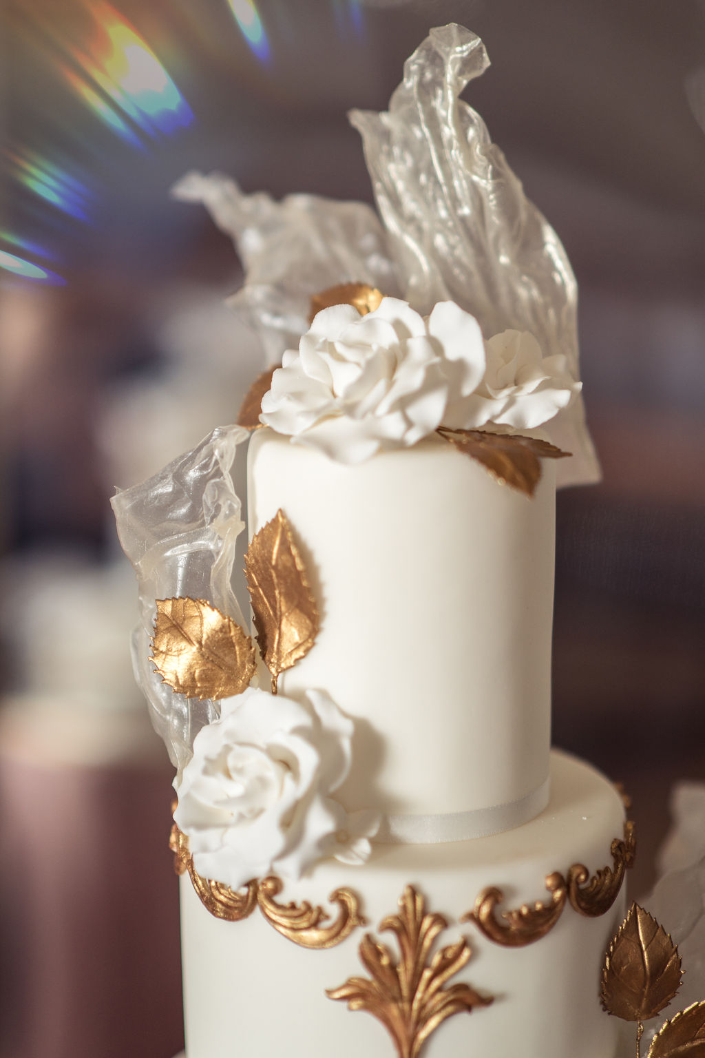 Ornate 3 tier gold and white wedding cake with white sugar flowers for movie themed wedding day
