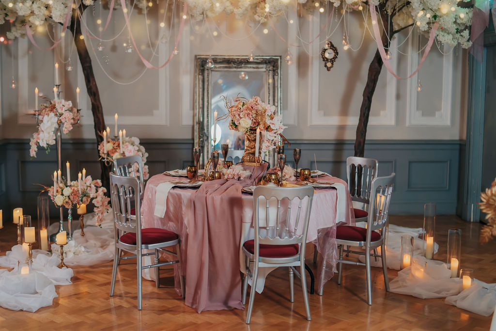 Dramatic themed wedding table centrepiece with goblin and ornate gold detailing - movie themed wedding tablescape and backdrop by finishing flourishes