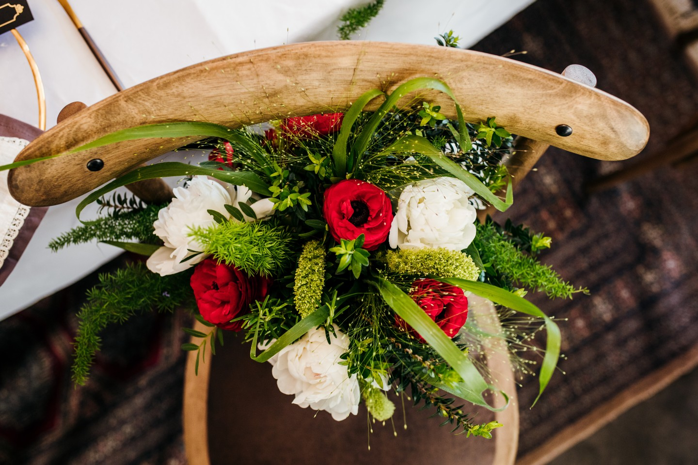 red and white wedding flowers on wooden chair