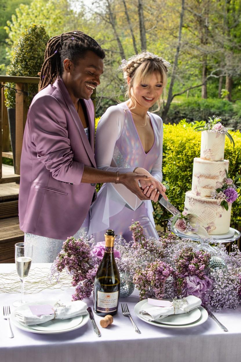 modern festival wedding - unique wedding wear - wedding jumpsuit - wedding catsuit - festival bride - unique wedding wear - bride and groom cutting cake - unique wedding table - purple wedding flowers
