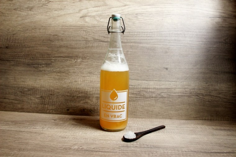 bouteille de kéfir avec des grains de kefir à côté