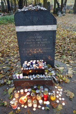 """Here rest the victims of the Warsaw Ghetto 1941-1943"" The plaque looks like a tombstone. The top is covered with stones and lighted candles cluster around its base"