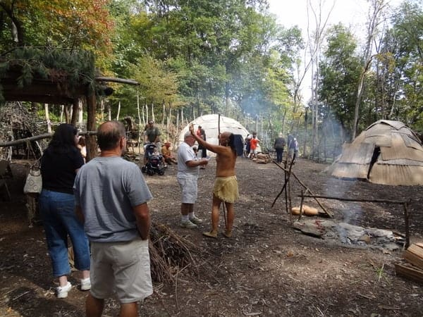 Visitors enjoy the recreated 16th-century Monongahela Village at the Meadowcroft Rockshelter and Historic Village in Avella, Pennsylvania