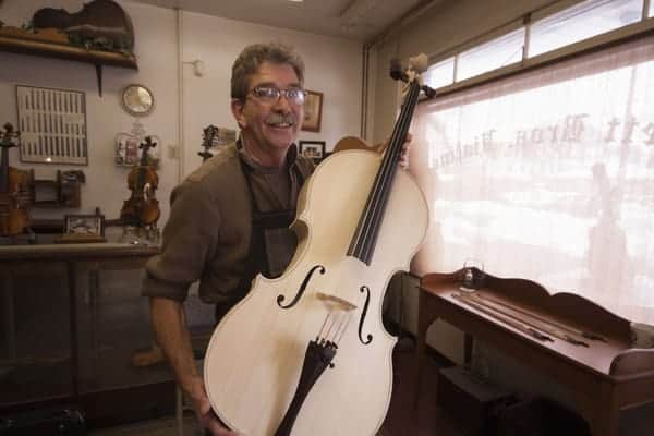 Mark Bluett with a cello at Bluett Bros. Violins in York, Pennsylvania