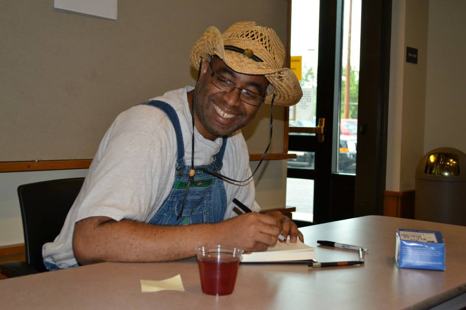 """Adrian Miller signs """"Soul Food"""" books in costume as a sharecropper"""