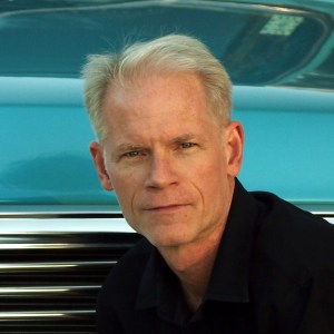 Pictured: Adam Gussow author photo; a head-shot of a man who has grey hair wearing a black shirt and kneeling in front of the grill of an automobile.