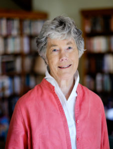 Pictured: Emily Herring Wilson author photo; a person can be seen standing in the foreground of a photo with bookshelves in the background; she is wearing a pink sweater over a white collared shirt, and has short grey hair and blue eyes.