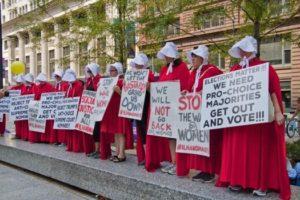 "Image caption: Charles Edward Miller, ""Illinois Handmaids Stop Brett Kavanaugh Rally Downtown Chicago Illinois 8-26-18"""