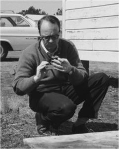 Billy Barnes inspects his camera while on site at the scene of a house fire in Craven County March 28, 1966 (P34_51905/C1_21); from the Billy E. Barnes Collection (P0034), North Carolina Collection Photographic Archives, The Wilson Library, University of North Carolina at Chapel Hill.