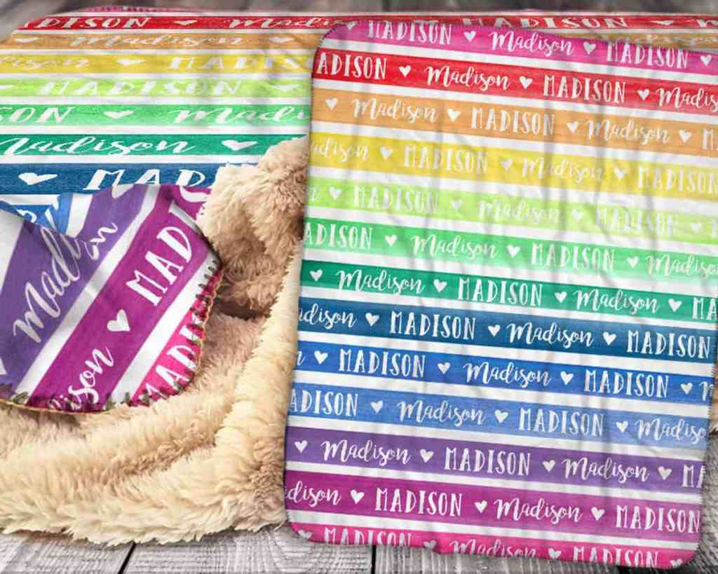 fuzzy-blanket-that-has-fuzz-on-one-side-and-straight-lines-on-the-other-side-that-make-a-rainbow-with-their-colors-this-blanket-is-customized-with-the-name-madison