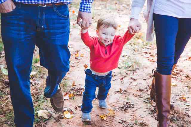 toddler-boy-with-huge-smile-walking-and-holding-parents-hands