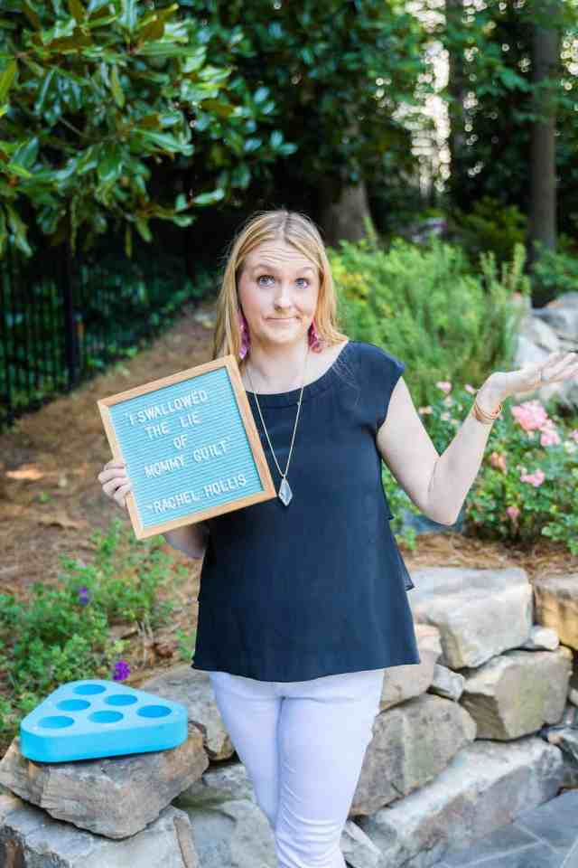 blonde-woman-holding-letterboard-with-a-quote-from-rachel-hollis-that-says-I-swallowed-the-lie-of-mommy-guilt