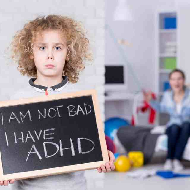 "young boy holds sign that reads ""I am not bad, I have ADHD"""