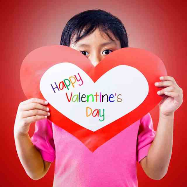"Young boy holds up a heart-shaped piece of construction paper that reads ""Happy Valentine's Day"""