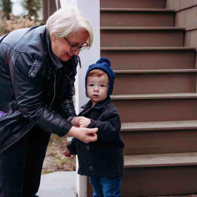 A nanny puts a coat on a little boy.