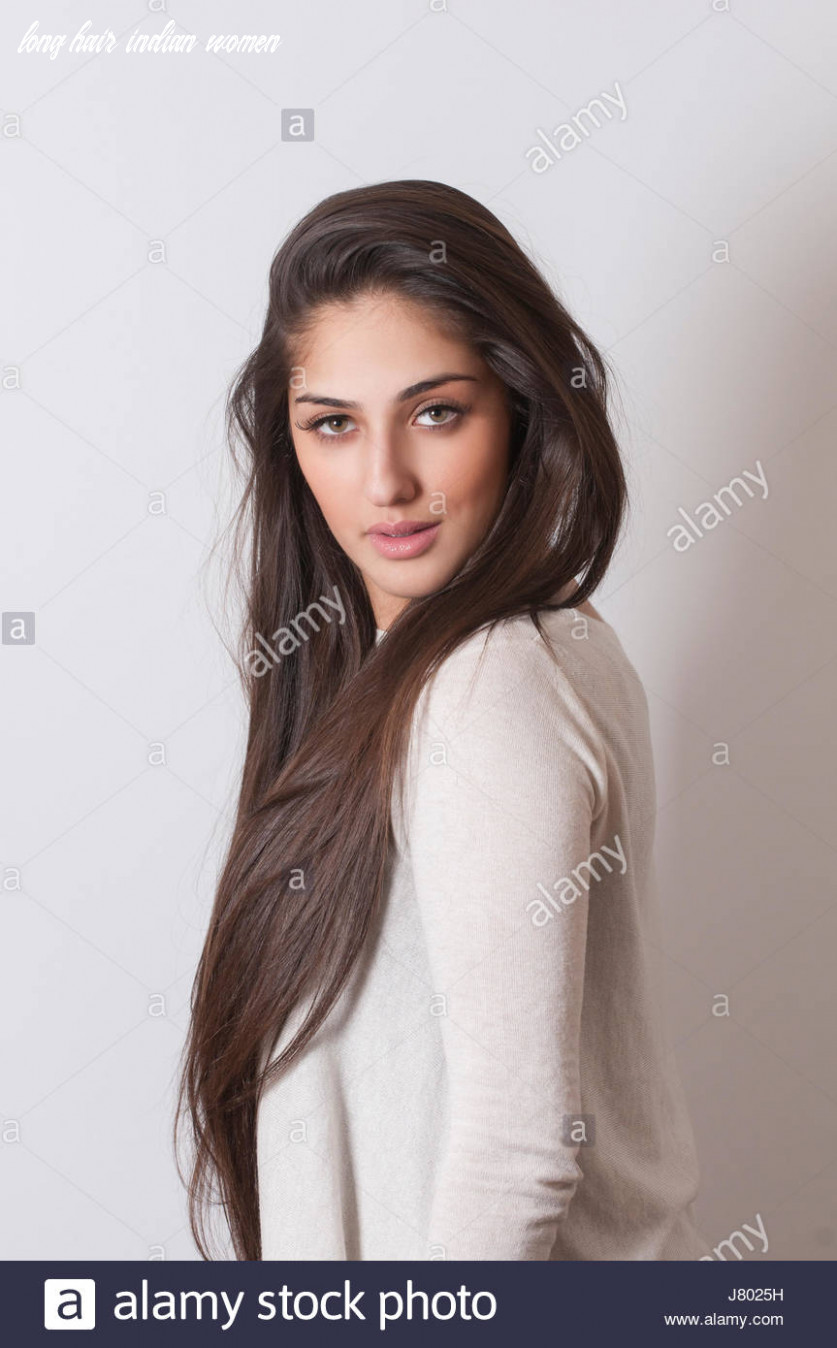 Beautiful Indian woman with long silky hair looking over shoulder ...