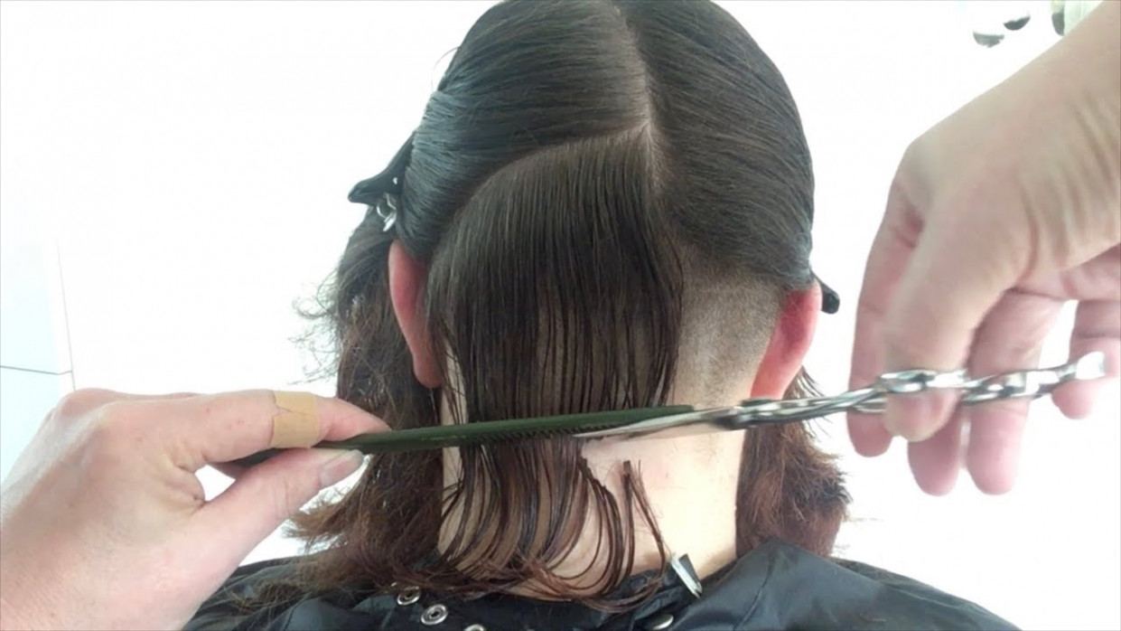 A curly bob haircut with shaved undercut