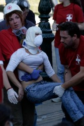 ATHENS, GREECE - OCTOBER 20: Paramedics carry a wounded woman to an ambulance in Athens' main Syntagma Square, during violent demonstrations on October 20, 2011 in Athens, Greece. On the second day of a 48-hour general strike against austerity measures being debated today in parliament, police fired tear gas and stun grenades as hundreds of masked youths attacked peaceful demonstrators from a Communist-backed trade union who had tried to isolate them from the rally.  (Photo by Milos Bicanski/Getty Images)