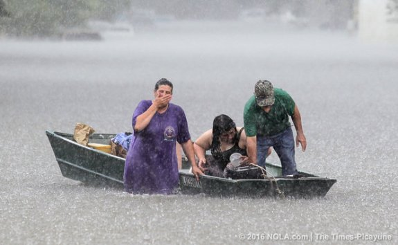 The heavy rainfall gives a family trouble when transporting their belongings. (Photo by David Grunfeld, NOLA.com | The Times-Picayune)