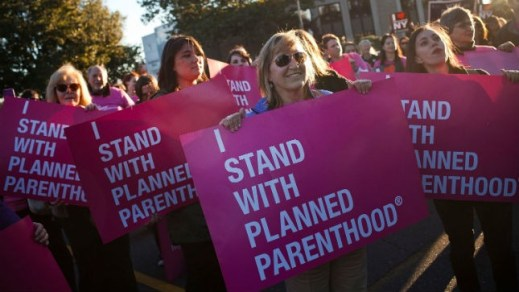Supporters of Planned Parenthood hold signs at a rally. Source: Getty Images
