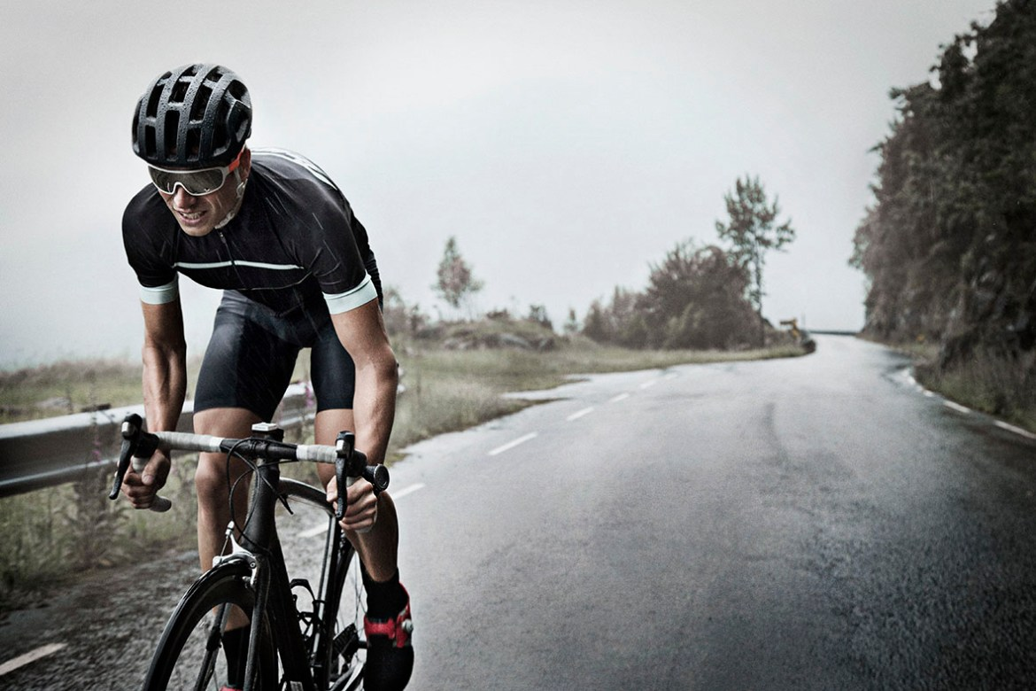 Male race cyclist driving up mountain road