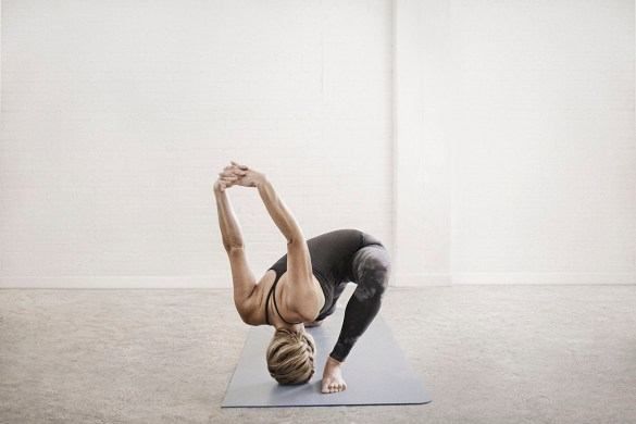 A blonde woman in a black leotard and leggings, standing on a yoga mat in a room, doing yoga, kneeling with her legs apart and her arms raised.