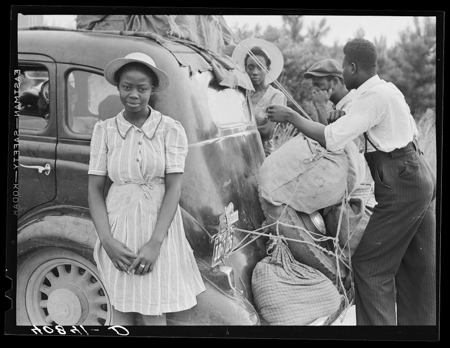 Black and white photograph of an African American family packing up their car during the Great Migration. A young woman is in front wearing a dress and smiling at the camera. Behind her, two men are putting luggage in the trunk of the car. In the background is a second young woman looking at the camera.