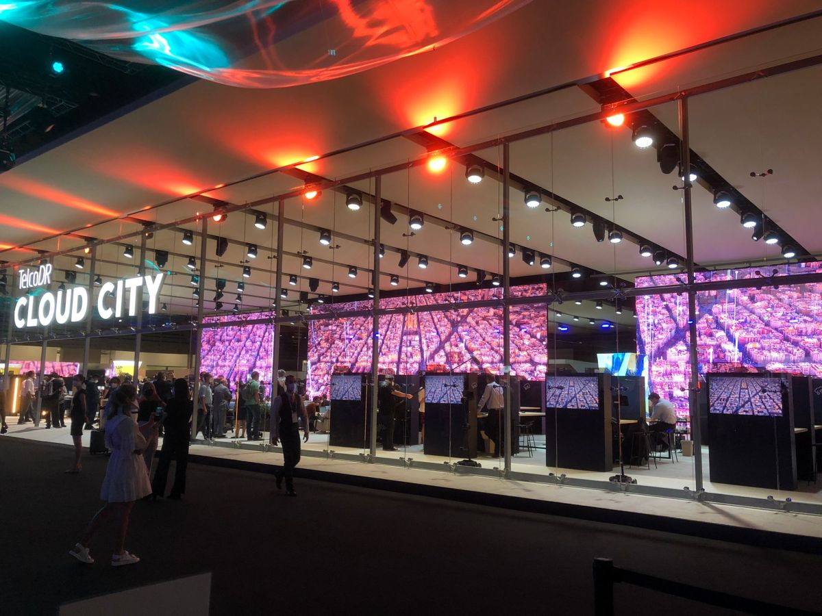Inside Cloud City. Exhibitor booths behind large glass area with a big Digital screen changing images and lighting effects in the area.
