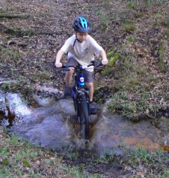 Tyler rides through the creek