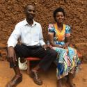 a man and a woman sitting in front of a clay wall
