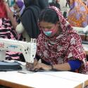 bangladesh woman sewing with a mask on