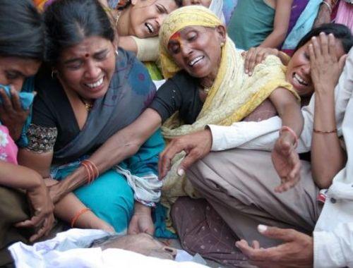 woman around an elderly deceased man India