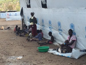 Refugees in Uganda sit by UNHCR wall