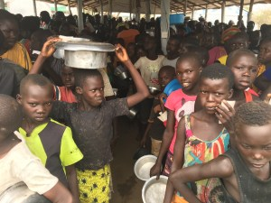 Refugee children in Uganda wait for food