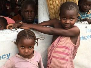 Refugee children in Uganda look at camera
