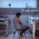 Man sitting between two hospital beds