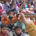 A violin in neck front of listening students