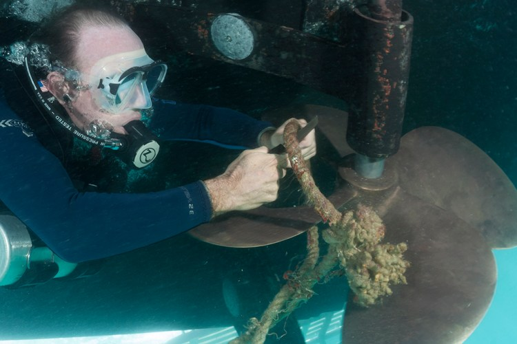 A diver using a small dive knife to cut the rope away from a fouled propeller.