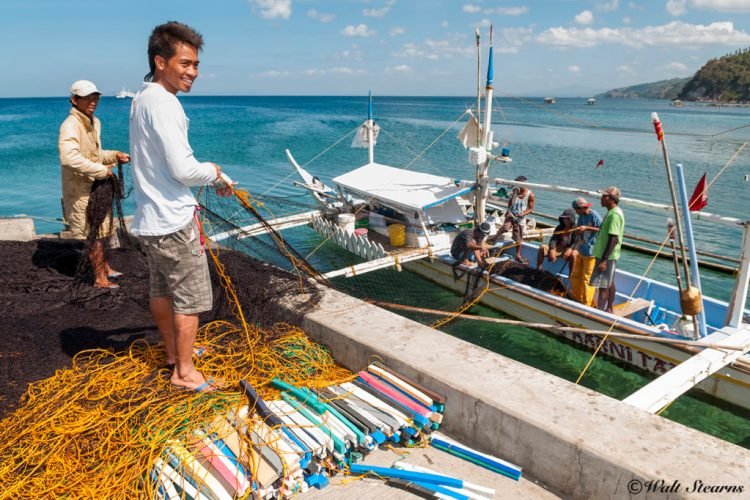 Local fishermen working on their nets at Anilao Pier.