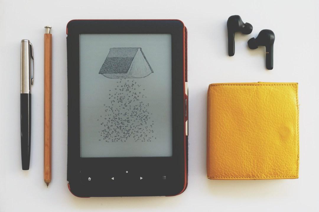 A minimalist flatlay of things: pen, pencil, ebook reader, purse, wireless headphones