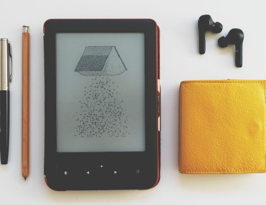 A minimalist flatlay of things: pen, pencil, ebook reader, purse, wireless headphones