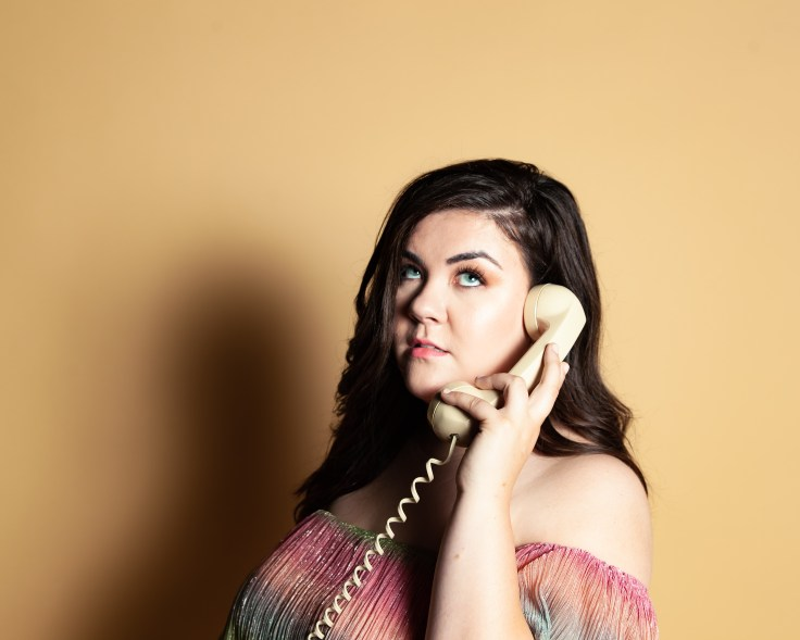 Nicole Miller is holding a phone rolling her eyes.  She knows she should hang up, but can't because she is hung up on him. This this story behind her first single.